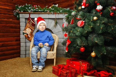 Boy in hat sitting in wicker chair near Christmas tree and gifts Stock Photo - 24236886