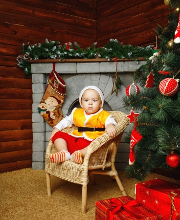 Boy in hat sitting in wicker chair near Christmas tree and gifts Stock Photo - 24236887