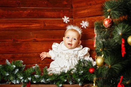 Cute little girl dressed as snowflakes near the Christmas tree and decorations Stock Photo - 24374368