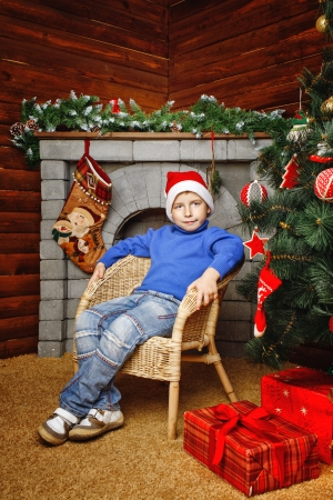 Boy in hat sitting in wicker chair near Christmas tree and gifts photo
