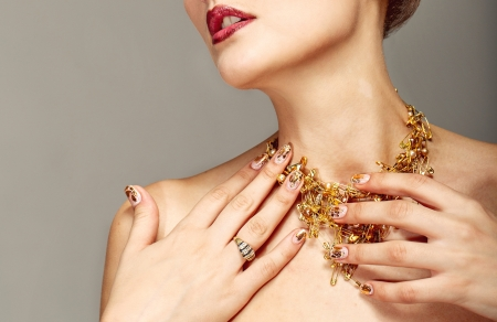 irrecognizable: Trendy nail design and beautiful necklace of golden pins safe