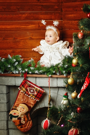 Cute little girl dressed as snowflakes near the Christmas tree and decorations photo
