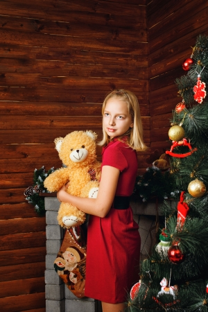 embracement: Young girl holding teddy bear and stands near Christmas tree