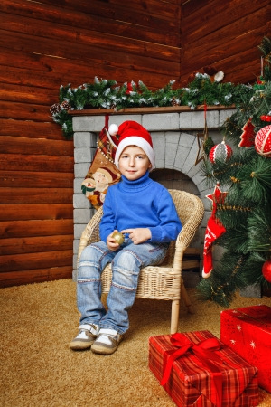 Boy in hat sitting in wicker chair near Christmas tree and gifts Stock Photo - 24381498