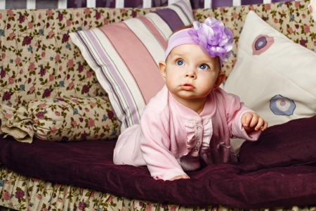 babygro: Little girl with bow on her head sitting on couch