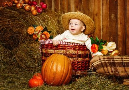 Little girl in straw hat sitting in a wicker basket near pumpkins photo