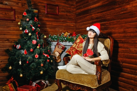 Girl with lollipop in her hand sitting on chair near Christmas tree photo
