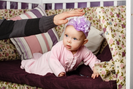 babygro: Little girl sitting on couch, and father stretches out his hand Stock Photo