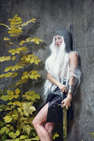 Attractive gray-haired maiden warrior in armor with sword in hand Stock Photo