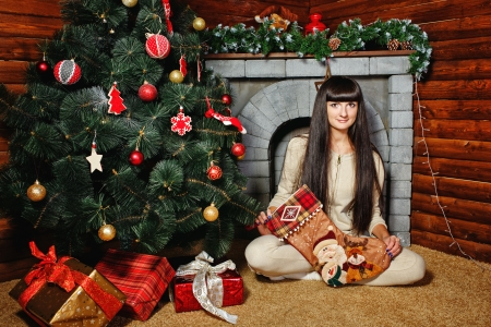Attractive young woman holding gift and sits near Christmas tree photo