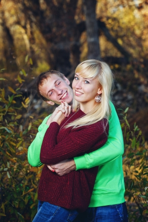 embracement: Young couple tenderly and lovingly embrace each other in autumn park Stock Photo