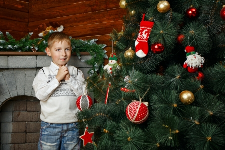 Boy decorates Christmas tree with festive toys and garlands
