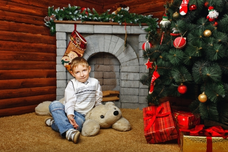 fireplaces: Boy sitting on teddy bear next to Christmas tree and gifts on a fireplaces