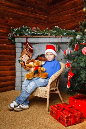 fireplaces: Boy sitting in wicker chair near Christmas tree on a fireplaces