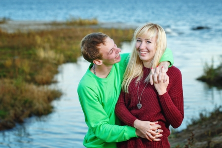 embracement: Young couple tenderly and lovingly embrace each other on banks of river Stock Photo