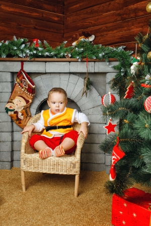 fireplaces: Little boy sitting in wicker chair near Christmas tree on background of fireplaces