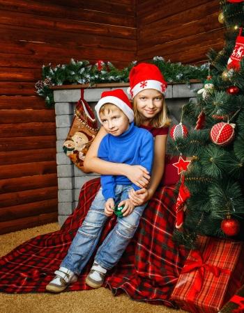 Girl hugs her little brother near Christmas tree Stock Photo
