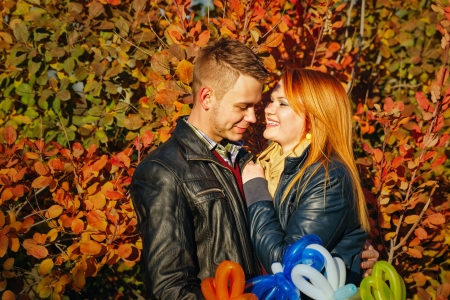 Young couple tenderly and lovingly looking at each other in autumn park Stock Photo