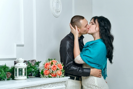 Passionate kiss of young couple near bouquet of roses photo