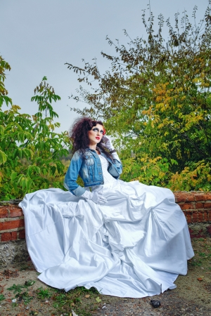Beautiful bride in wedding dress and denim jacket in autumn park