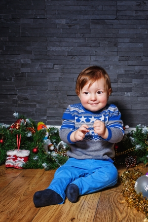 Little boy sitting on the floor surrounded by Christmas decorations Stock Photo