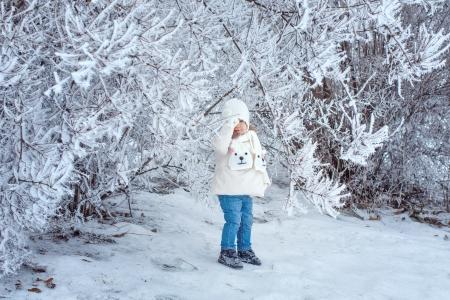 Little cute girl walking in winter forest alone photo