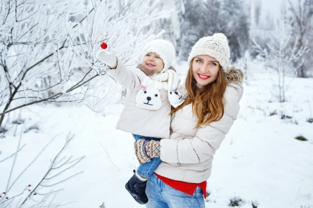 Mother holds daughter in her arms in the winter forest photo