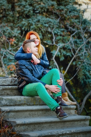 embracement: Attractive young couple sitting on the steps and hugging each other Stock Photo
