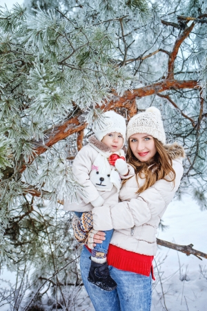 Mother holds daughter in her arms in the winter forest