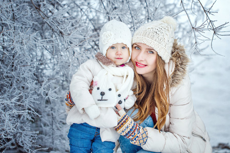 Young mother holding a daughter in a winter forest for a walk