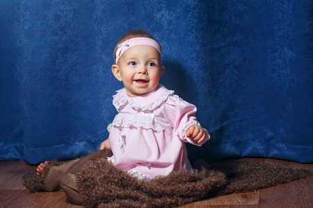 Pretty blue-eyed girl in a pink dress sitting on the floor photo