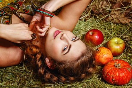 Attractive young rural girl in the hayloft after harvest festival photo