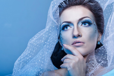 frostbitten: Attractive young girl with a theatrical makeup on the face in the image fabulous snow queen Stock Photo