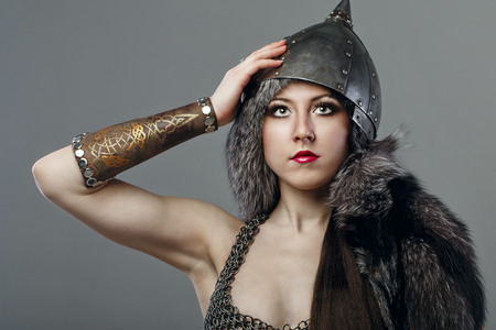 Attractive young girl with historical armor shot in studio photo