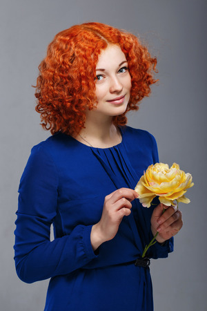 Attractive young red-haired girl in a blue dress holding in her hands a yellow flower Stock Photo - 25964490