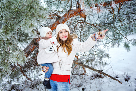 sleet: Attractive young mother holds daughter on hands and shows the side