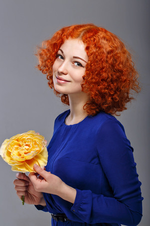 Attractive young red-haired girl in a blue dress holding in her hands a yellow flower Stock Photo - 26072958
