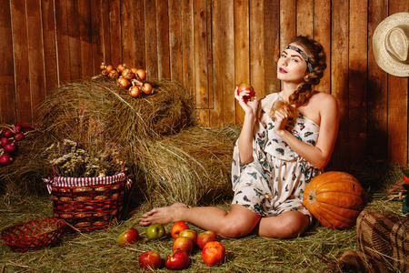 Attractive young girl sitting barefoot on the hay in the barn photo