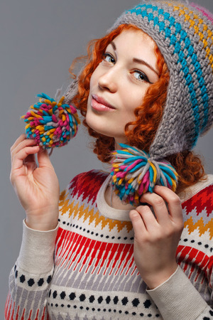 Attractive young red-haired girl in a warm knitted hat photo