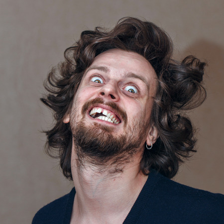 Man in a state of madness, shaggy with a grin on his face Stock Photo