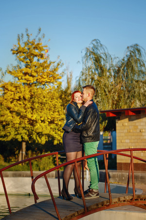 Young couple embracing standing on the bridge in the city park photo