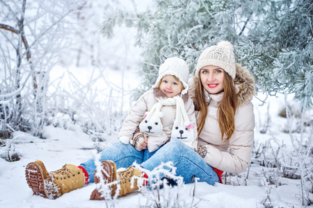 Young mother and daughter laughing for a walk in winter forest Stock Photo