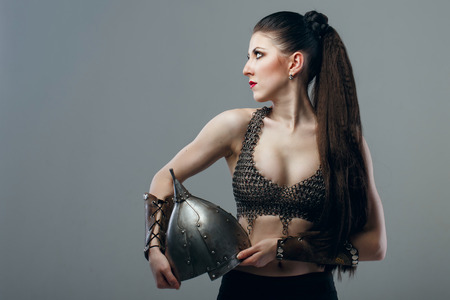 Attractive young girl warrior in chain mail holding helmet photo