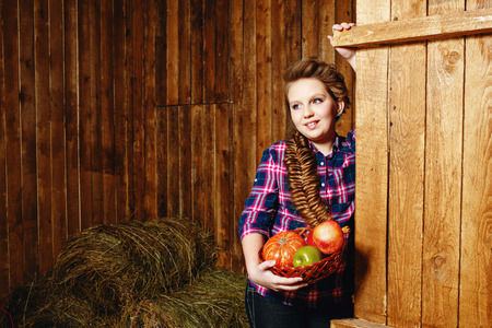 Teen girl with a plait in a barn on the farm after harvest photo