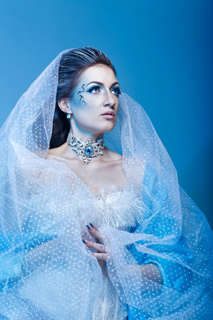 Attractive girl with scenic makeup in the image snow queen photo
