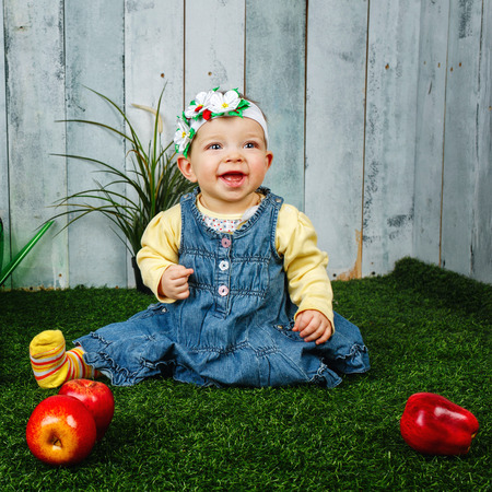 winesap apple: Little girl in the backyard sits on a lawn and smiling at her feet lie apples
