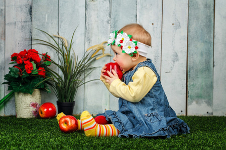 winesap apple: Little girl in the backyard sits on a lawn and eats an apple