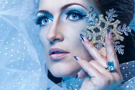 Girl with scenic make-up of the Snow Queen is holding a snowflake shot closeup photo