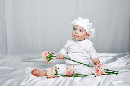 Little girl sitting on silk sheets lie at the feet of flowers Stock Photo