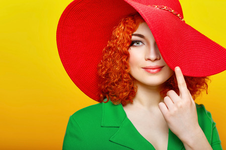 Attractive red-haired girl in red shady hat photo